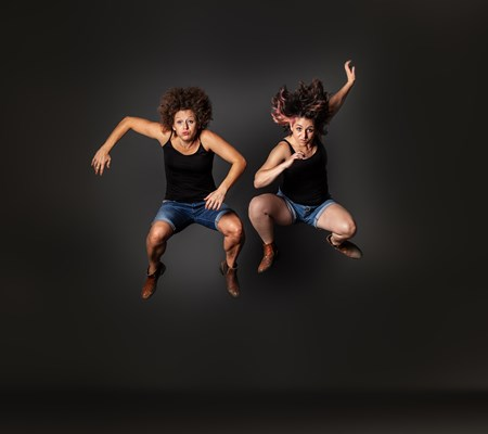 Two dancers mid jump facing the camera, against a black background